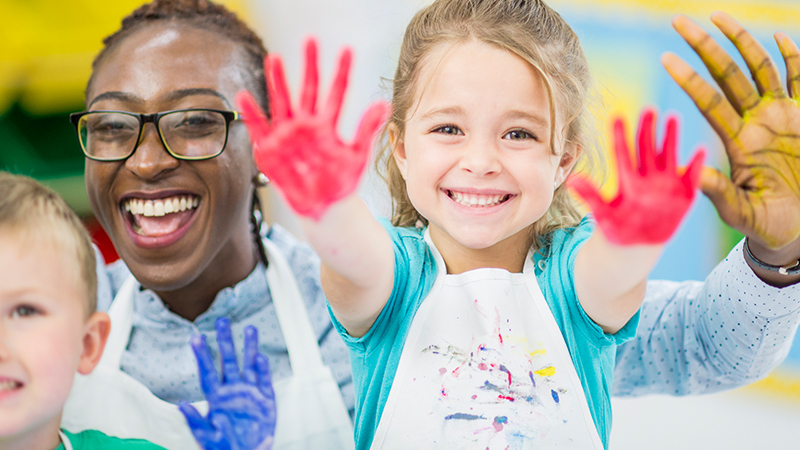 Teacher Rentention article featuring photo with student who has paint-stained hands.