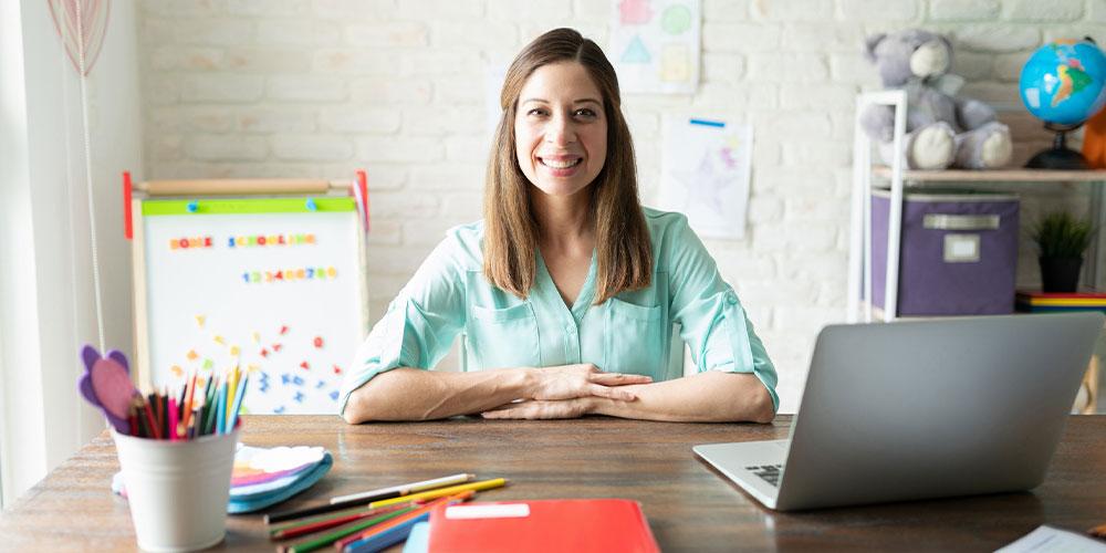 Woman, teacher sitting at desk